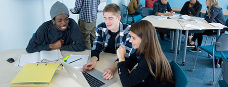 Students studying around a laptop