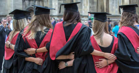 Graduates in gown with linked arms from behind