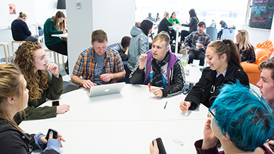 Students offering feedback at a round table
