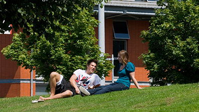 Students sitting on the grass outside the Health Centre
