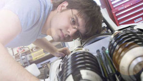 Engineering student looking at automotive equipment