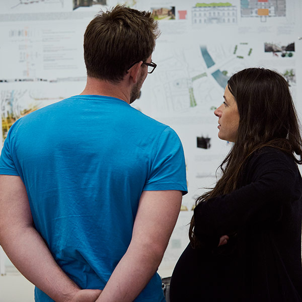 Two people looking at a wall of architecture work