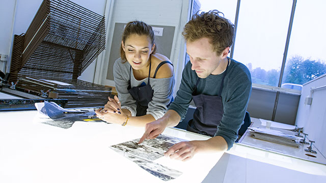 Students using a screen printer in an art studio