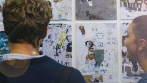 Two students looking at an exhibition of student art work