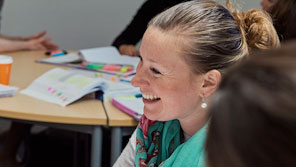 Student smiling while other students work in a small group