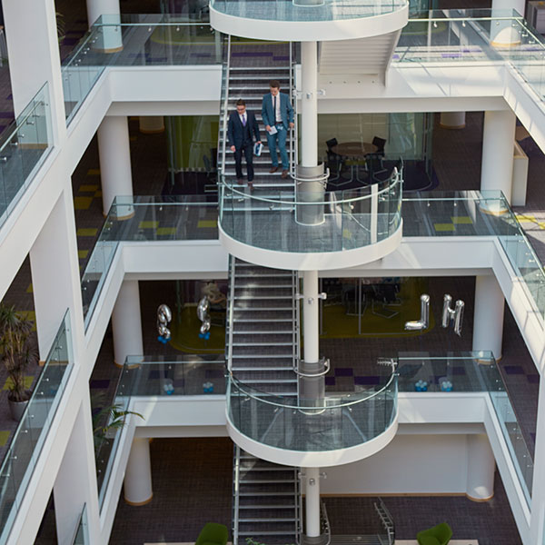Students on placement in atrium of modern office building