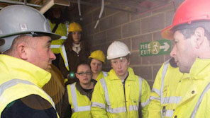 Builders wearing high-vis jackets in the basement of a building