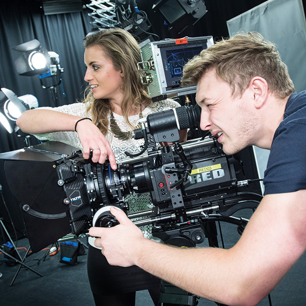 Filmmaking degree students using a camera