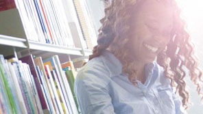 Smiling student standing in front of a book shelf
