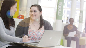 Two students conversing while using a laptop in a common