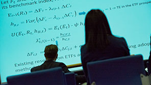 silhouette of two people looking at equations on a projector screen.