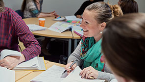 student smiling at other colleagues whilst sat around a table studying