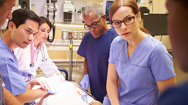 Health professionals discussing a patient's condition around the patient's bed