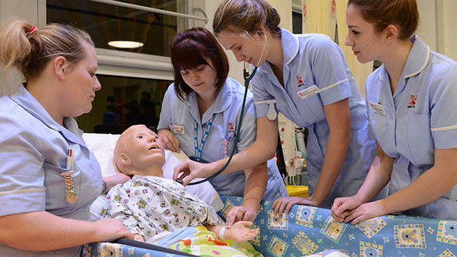 Nursing degree students treating a simulated patient