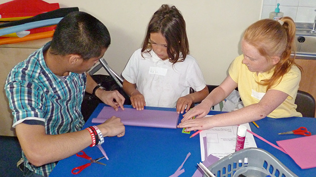 Male student doing craft with two primary school pupils