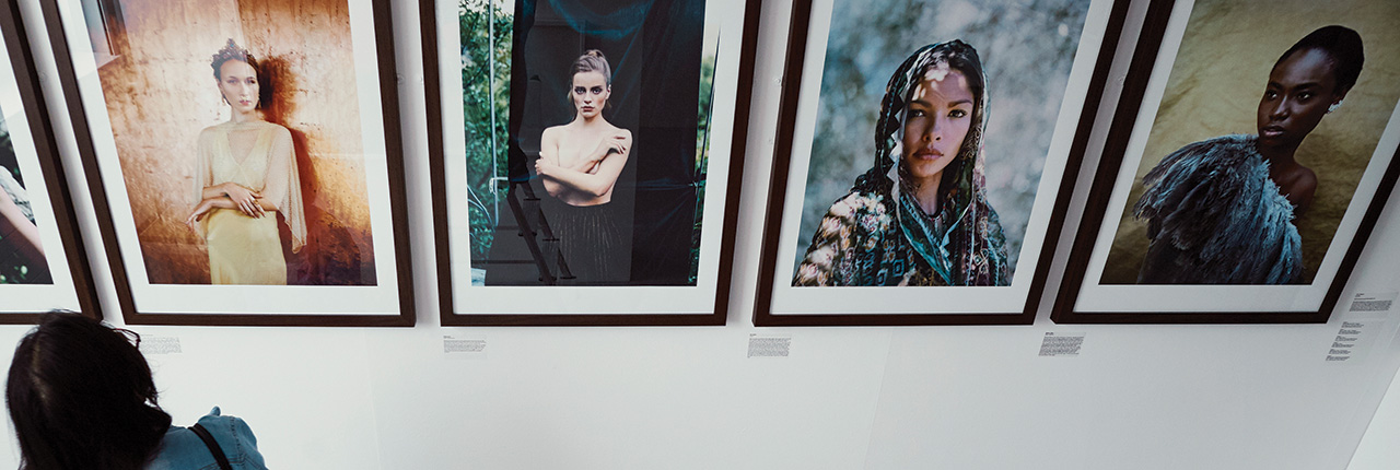 A female student looking at the photography degree exhibition