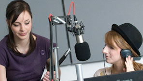 Two students using audio recording equipment in a studio within a journalism and media suite