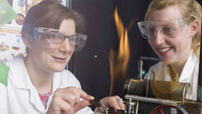 Two female scientists heating an item using a bunsen burner