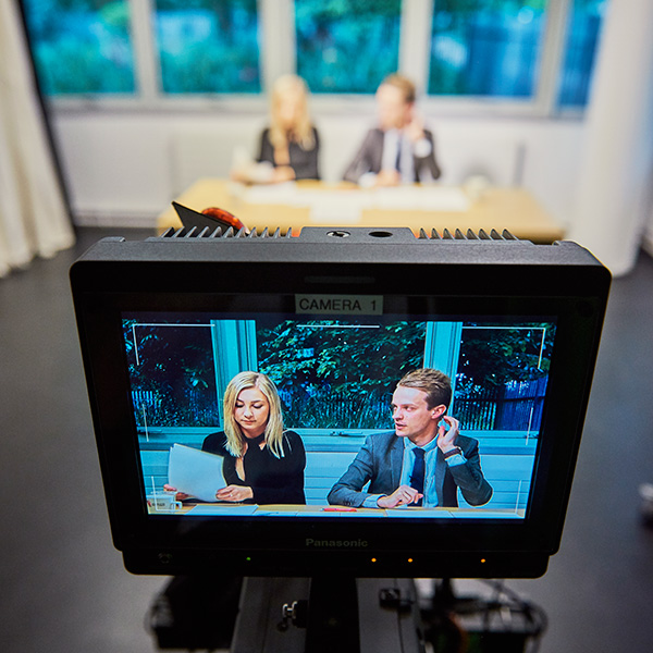 Students recording a TV programme within a journalism and media suite