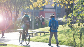 Student cycling through a leafy part of Frenchay Campus