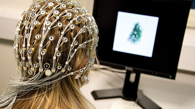 Student wired up to EEG machine with sensor hood