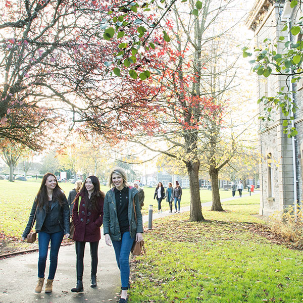 Students walking across Glenside Campus in the autumn