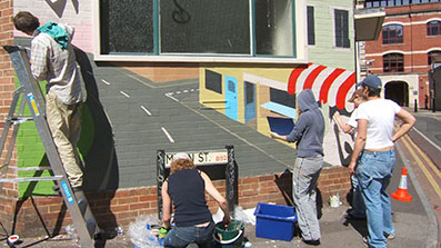 Students painting a mural onto a wall on a city-centre street in Bristol
