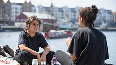 Two students sitting by the harbourside in Bristol city centre