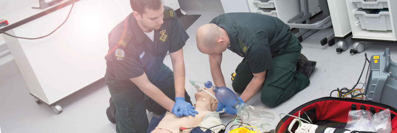 Paramedic students learning on a medical mannequin
