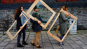 Architecture students carrying wooden frames