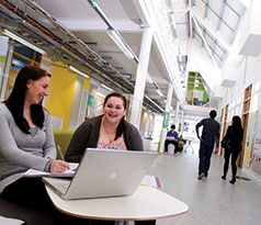Two female students sitting in the central area of the architecture building