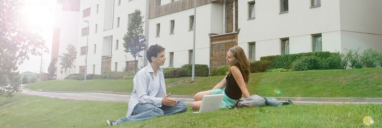 Couple sitting on grass outside an accommodation block