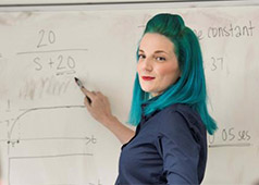 female teaching using a whiteboard to explain an equation