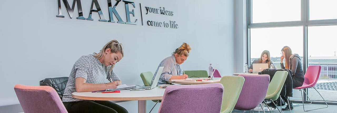 Students studying in a breakout space in the Bristol Business School building