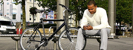 Man in central Bristol with bicycle leaning on bench