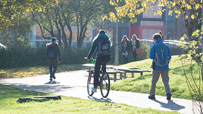 Students cycling and walking on campus