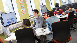 A group of students in a study room discussing a computer presentation