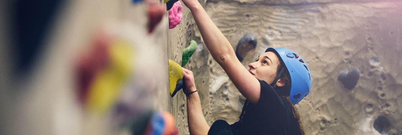 Climber scaling the climbing wall at the Centre for Sport