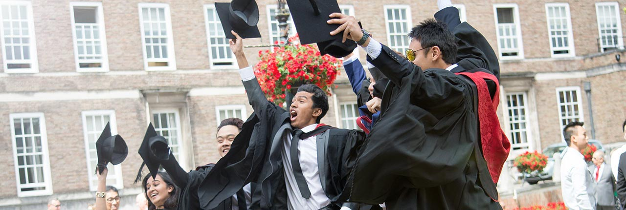 A group of students throwing their mortarboards in the air on their Awards Ceremony