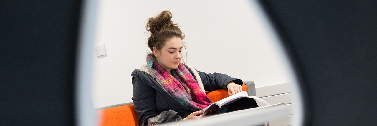 Student reading a textbook in the corner of a study room