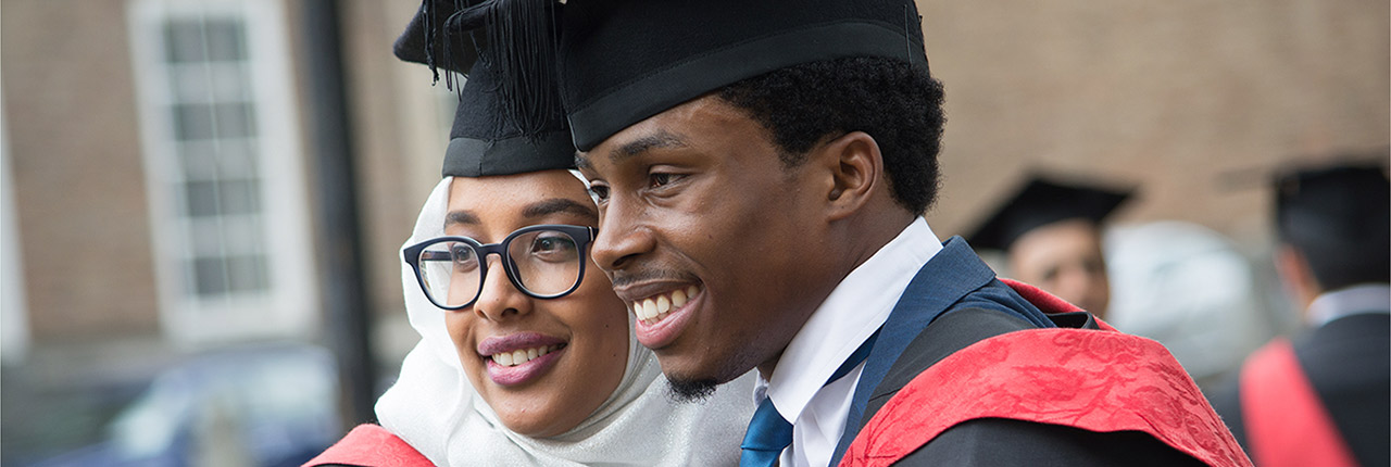 Two students posing outside at their graduation