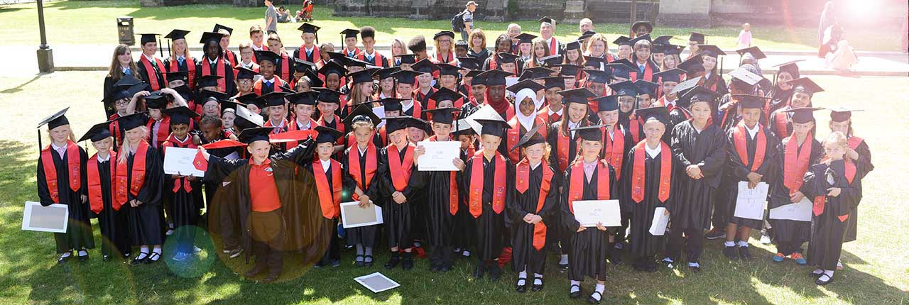 Children from Children's University having a graduation photo in graduation robes and hats.