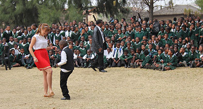 Student teacher dancing with school pupil in Africa