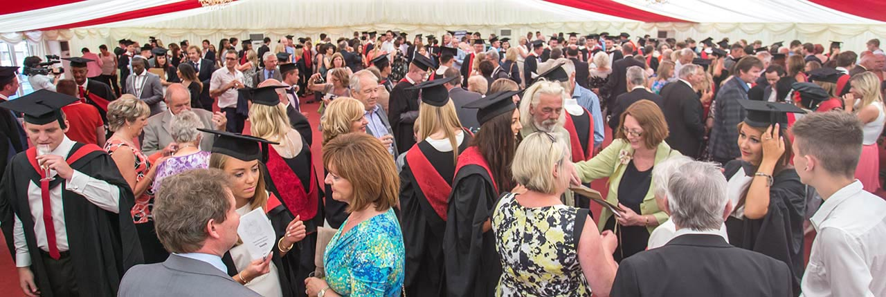 Graduands, parents and university staff networking in a marque