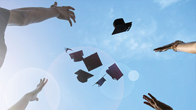 Mortar board hats thrown into the air