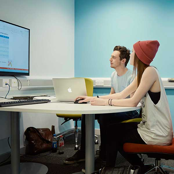 Two students working together at a desk looking at a computer screen