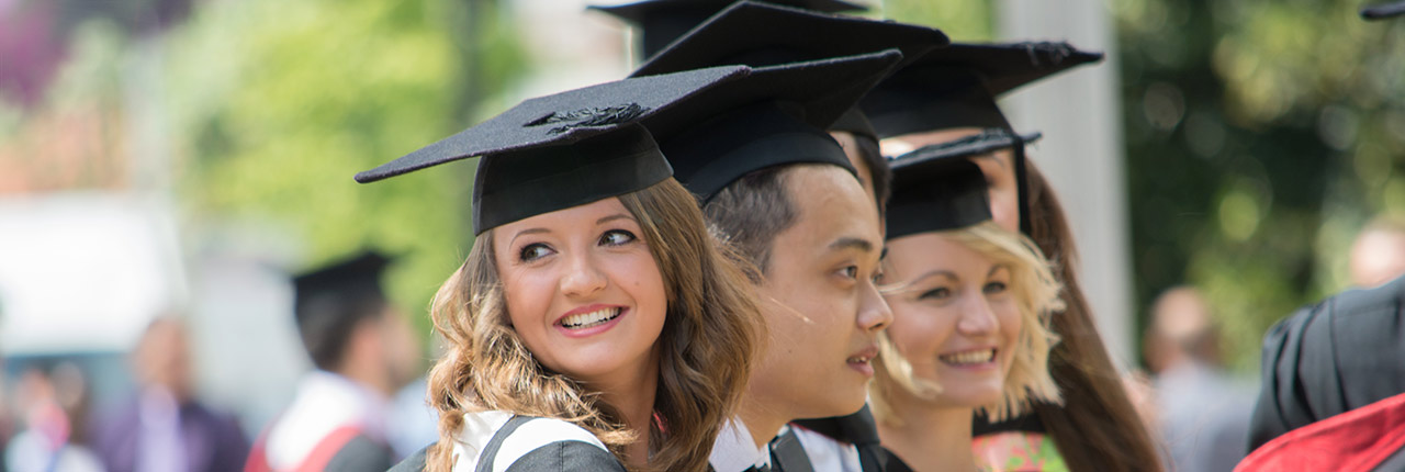 Smiling students wearing their graduation robes outside