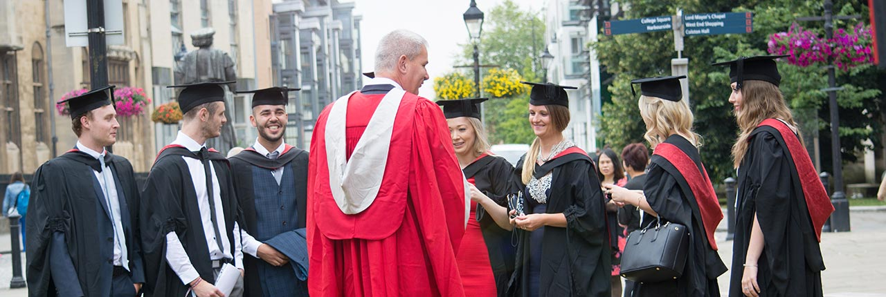 Graduands talking to a UWE Bristol member of staff in robes