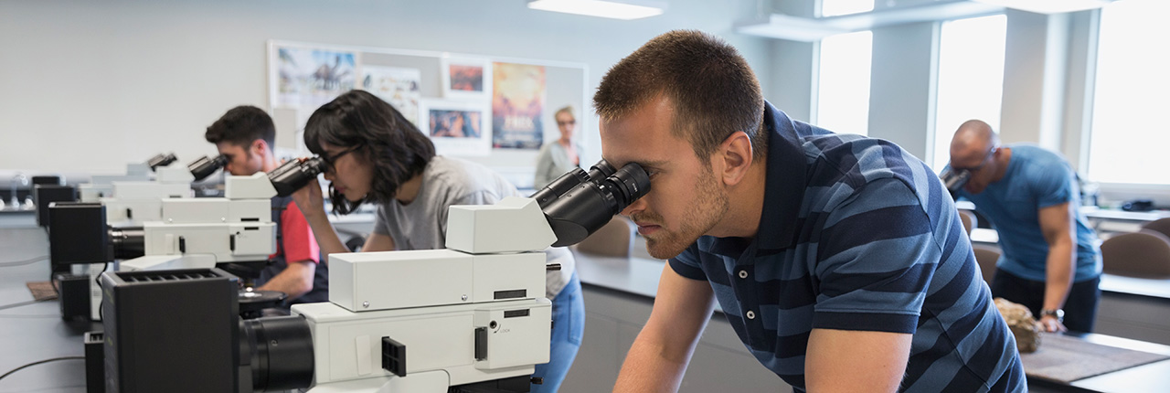Students using microscopes to study samples in a lab