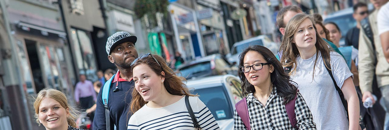 A group of international students walking down a street in central Bristol during an orientation event